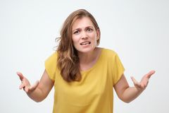 What do you want from me concept. portrait of unsatisfied angry emotional young woman in yellow t-shirt. Indoor studio shot, isolated on light gray background royalty free stock photo