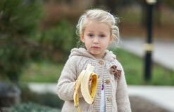 What do you want from me? Emotional girl child with a banana in stock photography