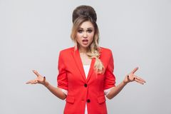 What do you want? Portrait of confused beautiful business lady with hairstyle and makeup in red fancy blazer, standing, looking at. Camera and asking. indoor royalty free stock photo