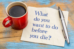 What do you want to do before you die?. Handwriting on a napkin with a cup of espresso coffee royalty free stock photo