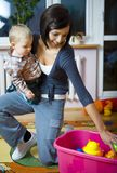 What do you want to play?. Young woman with baby boy during plaing. Woman taking toy from container. Front view stock photos