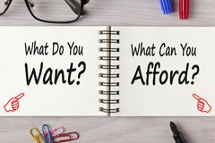 What do you want vs can you afford concept. What do you want vs can you afford written in notebook on wooden desk with marker pen and glasses. Business Concept royalty free stock image
