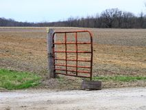 What is This Gate Keeping Out of the Field?. I always laugh when I see this gate and wonder why it stands in the middle of nowhere.  Truly unusual Royalty Free Stock Photo