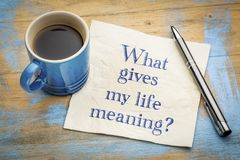 What gives my life meaning?. Handwriting on a napkin with a cup of espresso coffee royalty free stock photo