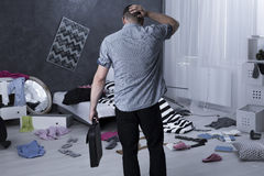 What happened here?. Man back view and chaos in apartment after burglary Stock Image