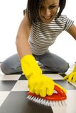 What a heavy dirt. Young woman in yellow rubber gloves kneeling and scrubs the floor. Focused on hand in glove with brush. Front view. White background stock photos
