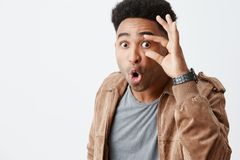 What the heck is going on. Close up of young dark-skinned man with afro haircut in casual stylish clothes being shocked Stock Images