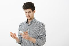 What the hell is that. Portrait of confused frustrated attractive male student with moustache in striped shirt, holding. Smartphone and gesturing with palm Royalty Free Stock Photography