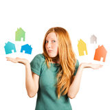 What house to choose ?. Red-haired girl facing a choice isolated on a white, holding coloured houses at her hands Royalty Free Stock Photo