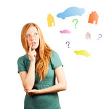 What house to choose ?. Red-haired girl thinking. isolated on a white, looking at coloured cars, houses and questions Stock Image