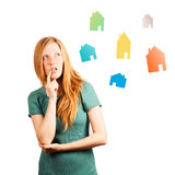 What house to choose ?. Red-haired girl thinking. isolated on a white, looking at coloured houses Royalty Free Stock Photos