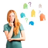 What house to choose ?. Thinking red-haired girl isolated on a white, coloured houses and questions at background Stock Image