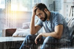 Sad exhausted man sitting and holding hand near head. What I have to do. Sad exhausted unshaken man sitting in the bright room feeling bad himself and holding Royalty Free Stock Images