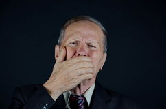 What I said! man closing his mouth with his hand. Man with hand closing his mouth on black background Stock Photos