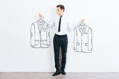 What jacket shall I choose?. Handsome young man choosing between two drawn jackets while standing against white background Stock Photo