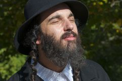 Portrait of young orthodox Jewish man with eyes closed. What is Judaism and how real Jewish Orthodox should dress and look like. Outdoor sunny bright portrait of stock photo