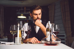 What kind of comment should I write. Attentive wine critic is sitting near table and tensely thinking about his recall Royalty Free Stock Images