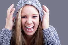 What a laugh. A pretty caucasian girl with blond hair wearing a hooded jersey raising her hands to her head and yelling in a sense of humor Stock Images