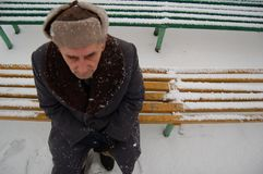 What is life. Old man sitting on the bench in the park focus on shoes stock photography