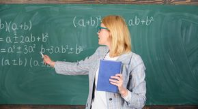 What makes great teacher. Teacher smart woman with book explain topic near chalkboard. School teacher explain things royalty free stock photos