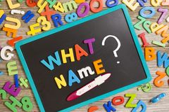 What name for a new baby, question on blackboard with many colorful plastic letters and positive pregnancy test stock photo