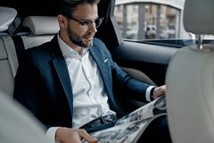 What is new in the world?. Handsome young man in full suit reading a newspaper while sitting in the car stock photo