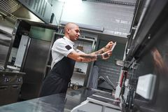What is next... Handsome bald male chef with tattoos on his arms looking at order list in a restaurant kitchen. royalty free stock image