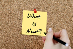 What is Next. Woman hand writing 'What is Next?' on adhesive note pinned on cork noticeboard Stock Photo