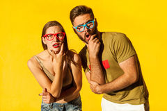 What?! People emotions and feelings. Handsome young adult hipsters, looking at camera with wonder face. Yellow wall, outdoor stock photography