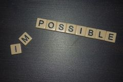 What is possible? Not impossible. Letter tiles lined up on black background with letters removed. stock photos