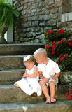 What's That?. Siblings sitting on stone steps of old rock house looking at something in little sister's hands Stock Photos
