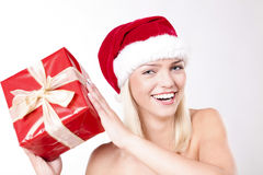 What's In The Box?. Cheerful Beautiful Blond Girl Wearing A Santa Hat And Holding A Present Stock Photos