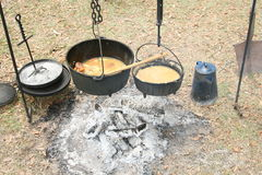 What's cooking. Cooking over open fire with cast iron pots Royalty Free Stock Photos