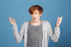 What`s going on. Young handsome redhead male student in casual grey outfit spreading hands with lost expression, don`t Stock Photos
