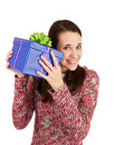 What's inside?. Young woman trying to figure out what's inside of the present Stock Photos