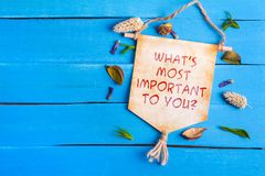 What`s most important to you text on Paper Scroll. What`s most important to you text on Canvas Paper Scroll with dried flower around and blue wooden background stock photo