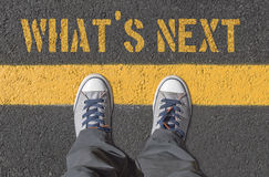 WHAT`S NEXT print with sneakers on asphalt road. WHAT`S NEXT print with sneakers on asphalt road, top view Stock Photography