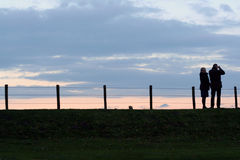 What's out there?. A couple on a dike, looking at something Royalty Free Stock Photo