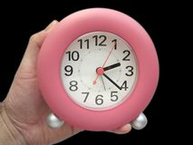 What's the time. Handheld pink clock, on a black background stock images
