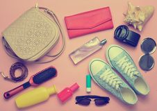 What& x27;s in the women& x27;s bag? Going on a trip. Girly fashionable spring and summer accessories: sneakers, cosmetics, beauty and hygiene products, a bag Stock Image