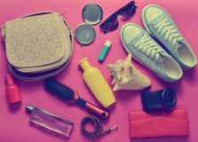 What's in the women's bag? Going on a trip. Girly fashionable spring and summer accessories: sneakers, cosmetics, beauty and hygiene products, a bag Stock Photos