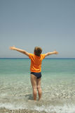 What a scope. Boy in orange t-shirt standing on shore spreading out hands Royalty Free Stock Images
