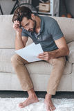 What shall I do with my budget?. Desperate young man holding papers and carrying glasses in his hand while sitting on the couch at home Stock Images