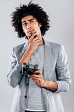 What shall I shoot next?. Handsome young African man holding retro styled camera and looking thoughtful while standing against grey background Stock Images