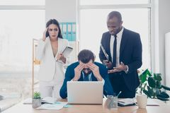 What a shit, oh no! Three shocked, depressed, professional agent. S in workplace, workstation, lost the tender, a lot of money, holding hands on head, looking royalty free stock photography