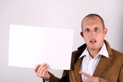 What A Shock. A young businessman is holding a sign in shock! White sign to write on Stock Images