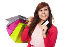 What should I buy more?. Dreaming woman with shopping bags and credit card Royalty Free Stock Images