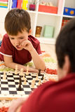 What should I do now - kid playing chess thinking Royalty Free Stock Photos