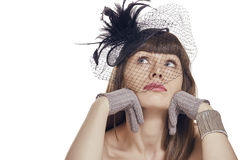 What should I do?. Pensive sad pretty young lady with fringe haircut wearing gloves and black vintage feather light hat with net veil. Retro styled woman Stock Images