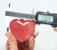 What size love?. Using calipers to exactly measure a crystal heart royalty free stock photo